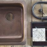 top view of rivera undermount doube bowl copper sink with faucet, drain, granite sample and cabinetry