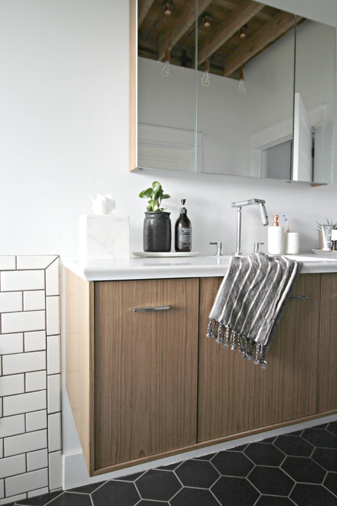 bathroom sink with light wood cabinets, white subway tiles, dark floor tiles