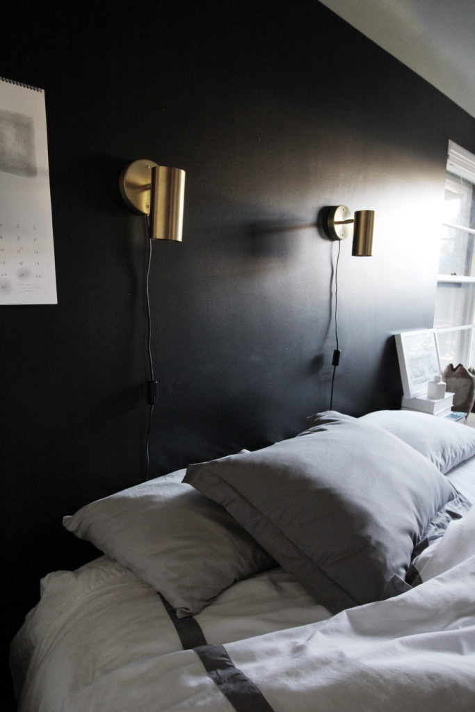 bedroom with dark walls, brass lights, gray bedspread