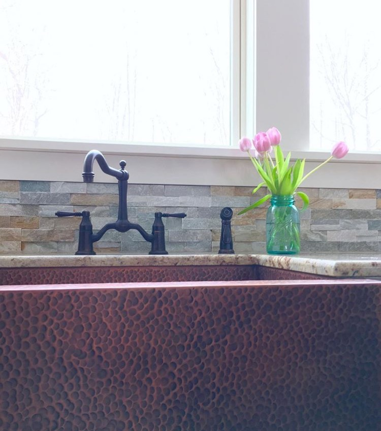 copper arpon front sink installed in granite countertop