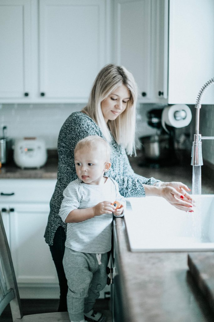 Mother washing hands at sink with child