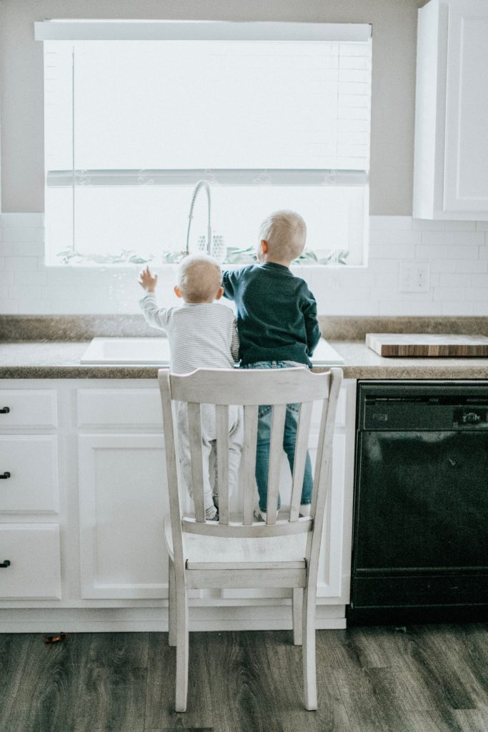 Children washing dishes at kitchen sink