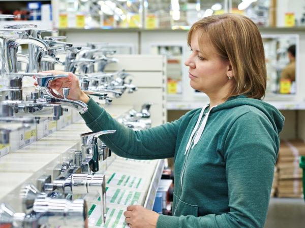 Woman shopping for bathroom equipment in DIY shop