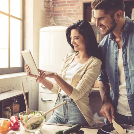 young couple looking at tablet while making a salad