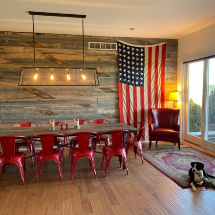 Dining room with red chairs, farm table & American flag