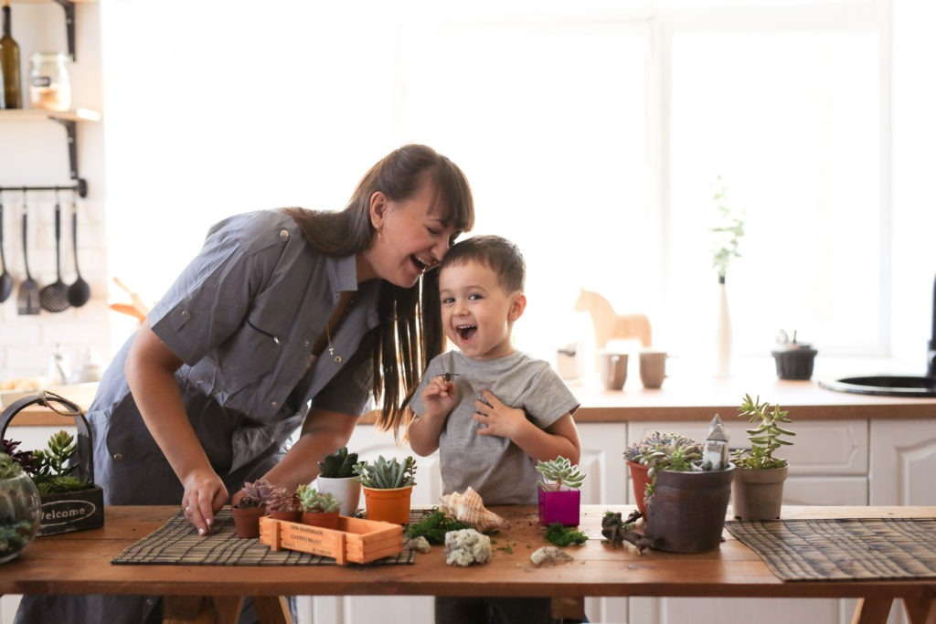 Cute child boy helps his mother to care for home plants. Mom and her son engaged in gardening near window at home.