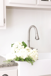 white farmhouse sink with white flowers